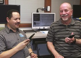 Instructor Hugo G. showing student Cliff S how to use voice technology on his phone.