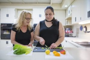 An instructor watches as a student chops vegetables