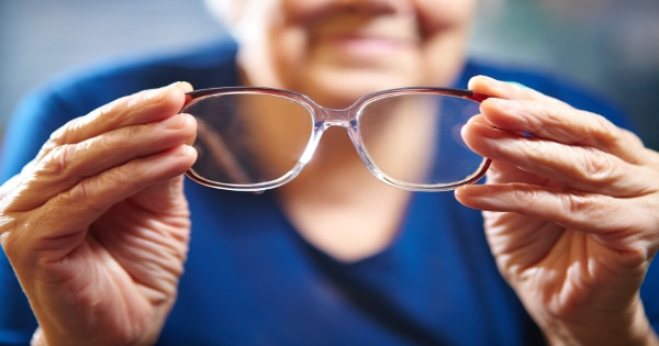 An older woman holding a pair of glasses