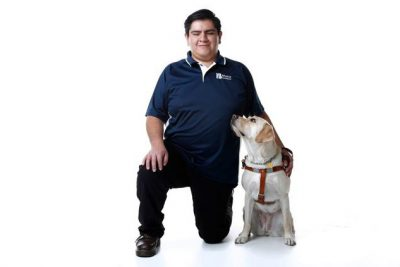 Braille Institute Techspert Daniel Ortiz Merino kneels next to his yellow lab guide dog and smiles at the camera