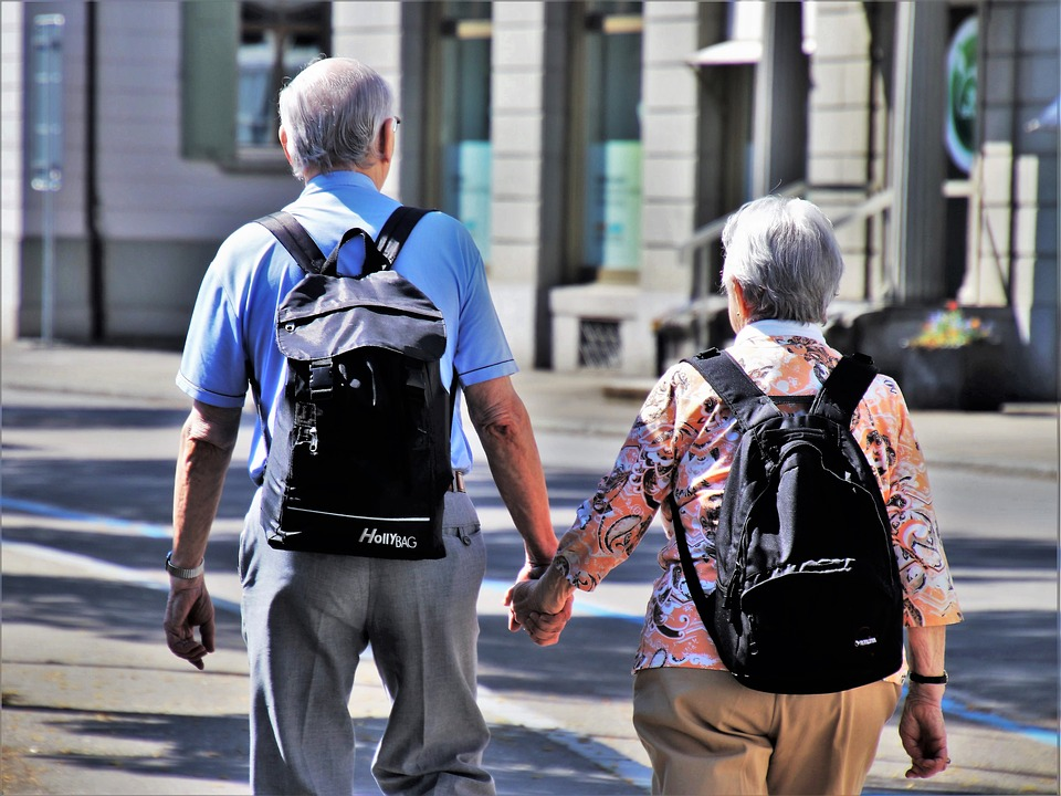 Elder couple walking and holding hands. Both have backpacks on.