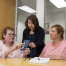 A Braille Institute staff member and two students look at a brochure