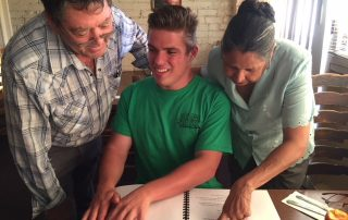 Mason Fessenden (middle) presents the braille menu he made for Rudy's Mexican Food to owners Rudy and Rosa Castrellon.
