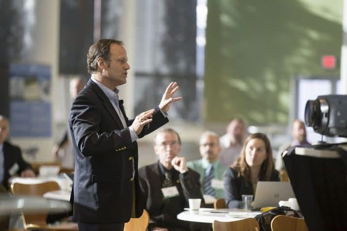 Man standing giving presentation to room of adults