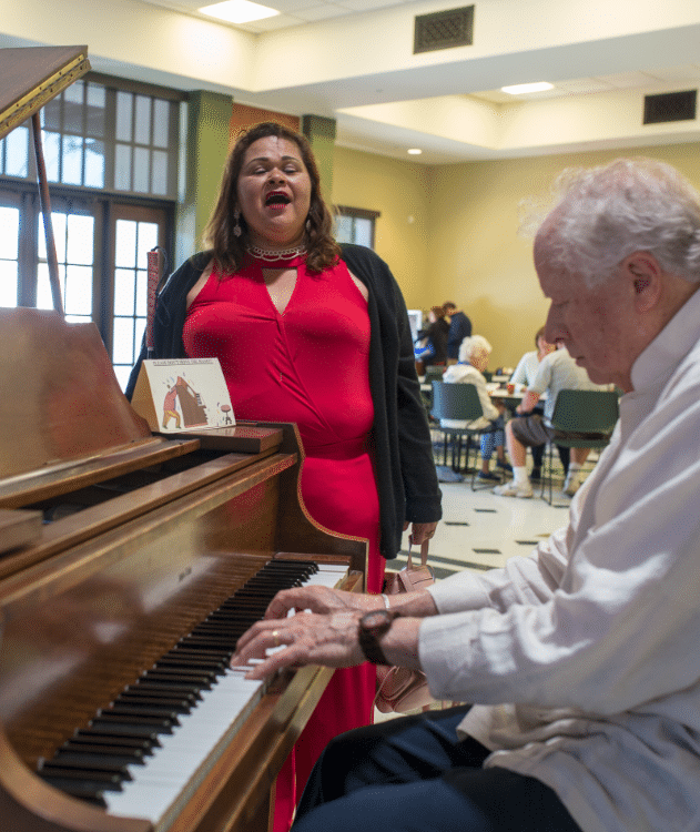 Connie R sings by the piano being played by music instructor