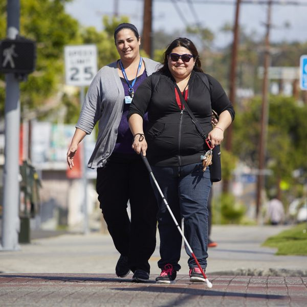 A woman with a white cane walks down the street with Orientation and Mobility Specialist, Tamar Tashjian, from Braille Institute