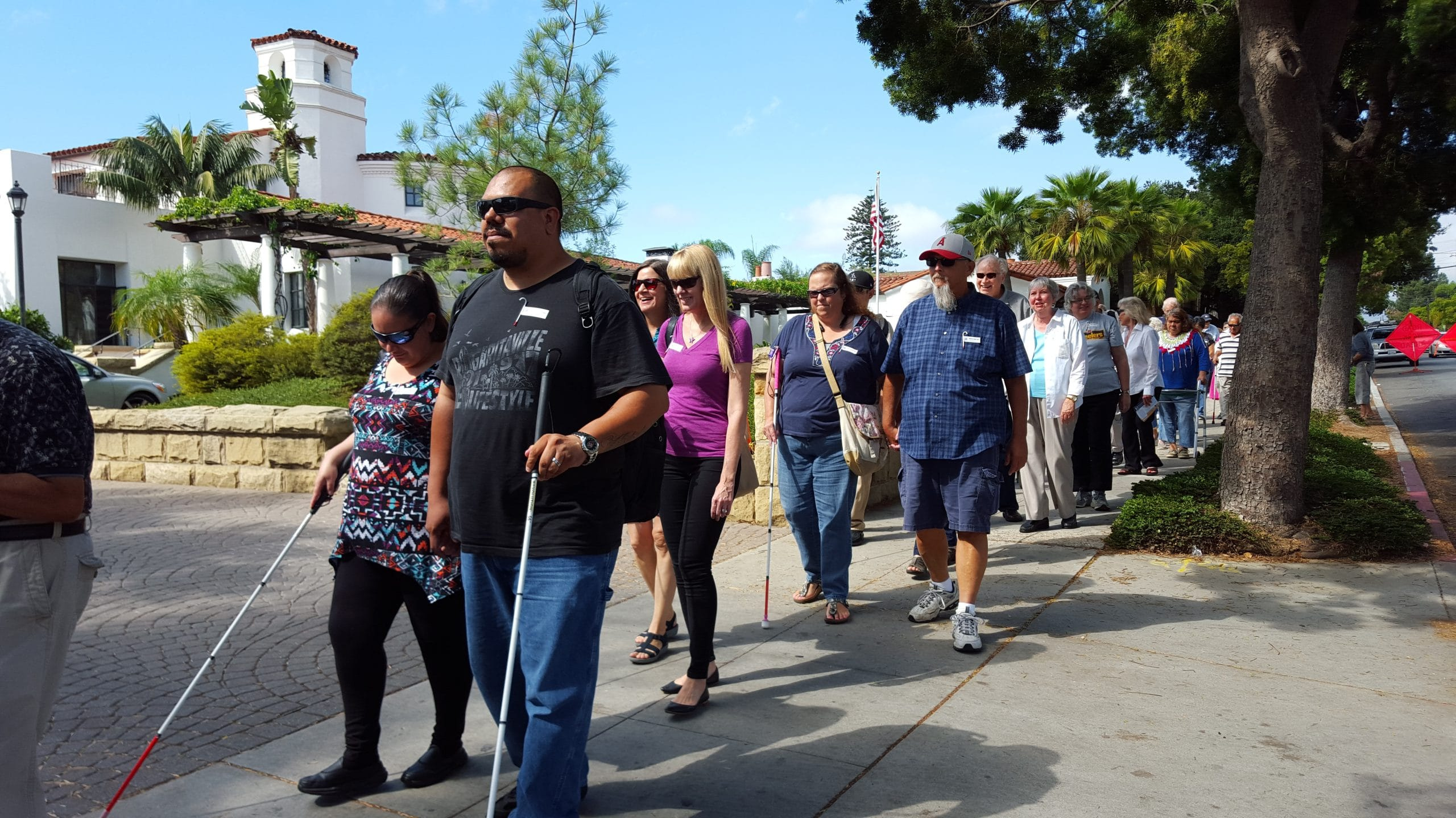 Students walk in pairs along the road infront of the Santa Barbara Center with their white canes