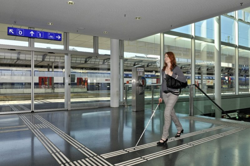 Woman walking with white cane in airport building