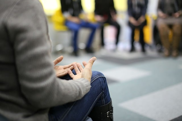A person's hands rests in their lap as they sit in a group circle