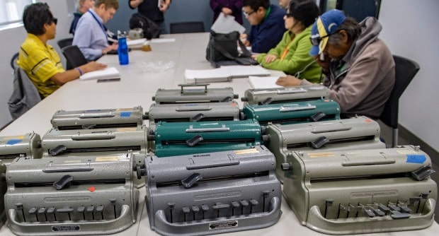 12 Braille typewriters on a table in a class room