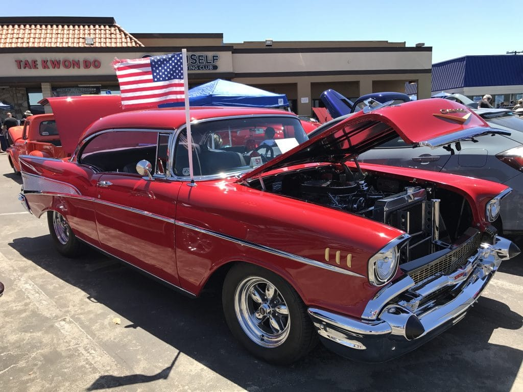 Classic red car, American flag waving on antenna, hood and trunk popped open