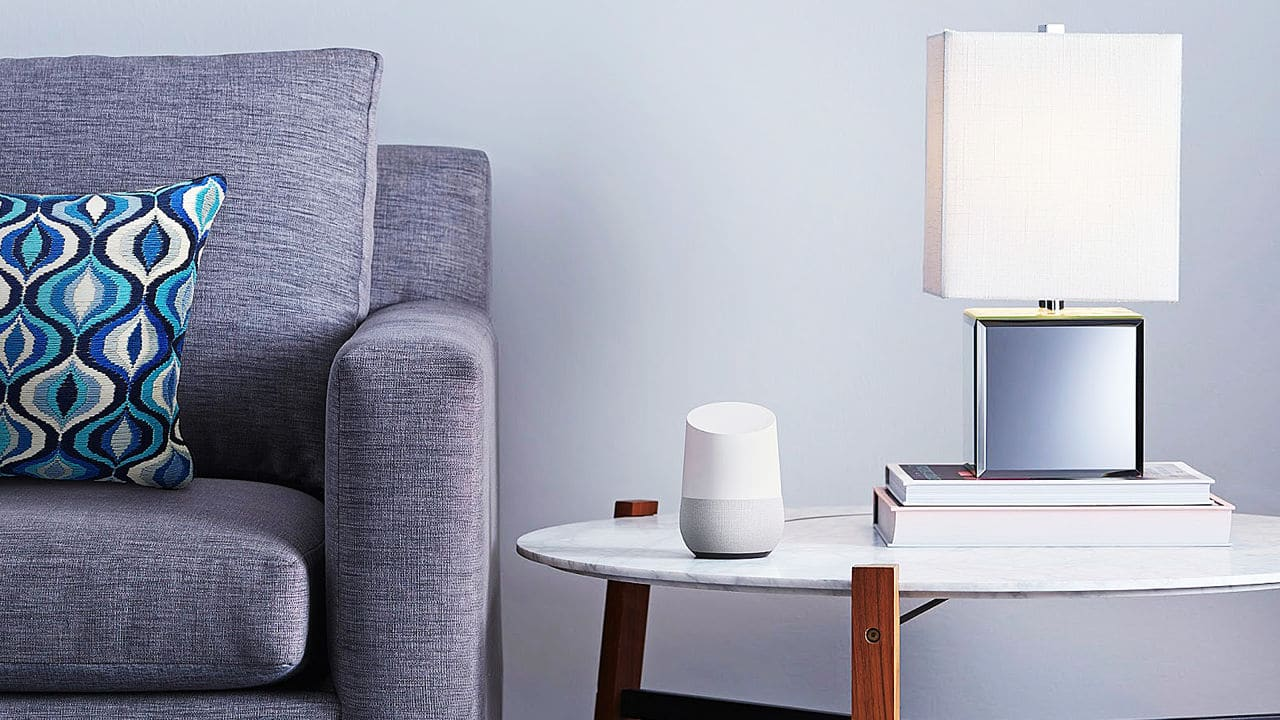 Couch on left, lamp sitting on table on the right, Google Home device in the middle resting on table.