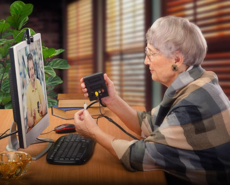 An older woman holds a device and cables in her hands as she listens to instruction from a remote session on the computer
