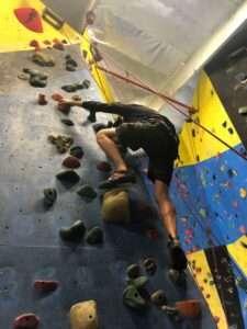Dan in the process of indoor rock climbing.
