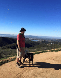 Dan standing with his guide dog outside on a trail.