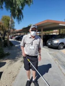 Photo of Jerry walking on sidewalk with white cane and COVID mask.